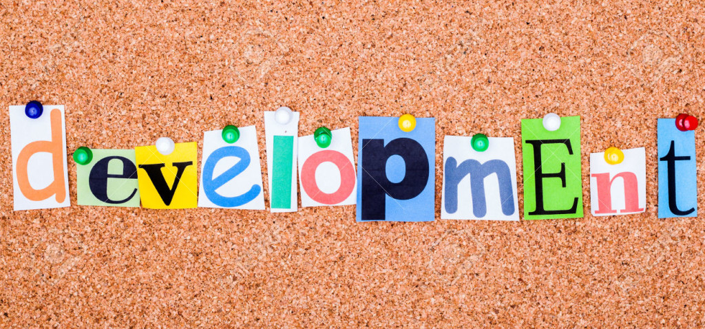 The word development in cut out magazine letters pinned to a cork notice board