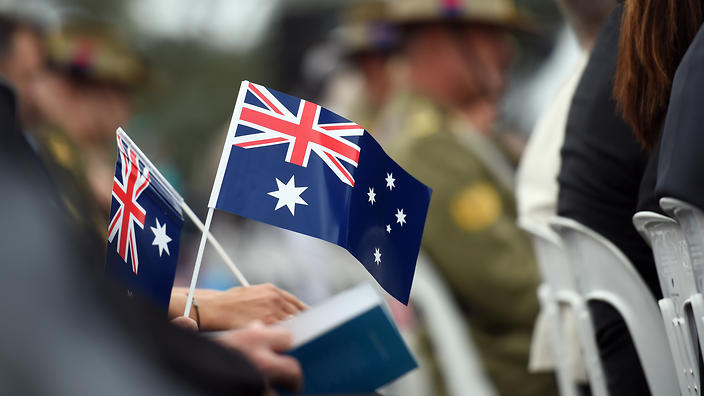 Memmbers of the public hold flags at an Australia Day Citizenship Ceremony and Flag Raising event in Canberra on Tuesday, Jan. 26, 2016. (AAP Image/Mick Tsikas) NO ARCHIVING